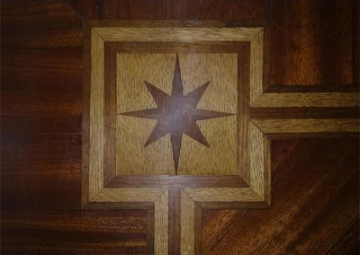 Black walnut marquetry star border corner detail and three line walnut and oak border in a mahogany double herringbone parquet floor in Halam near Southwell Nottinghamshire
