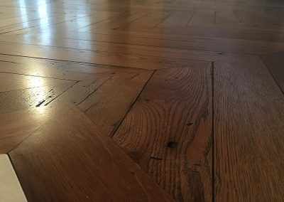Oak chevron parquet flooring and border detail up to a hearth with a stained and hardwax oil finish near Nottingham