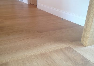 Prime grade Oak engineered planks 180mm wide joining in a doorway without a threshold in a modern contemporary house with oak doors and white skirting boards