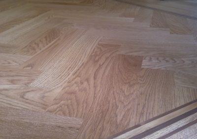 Oak herringbone parquet and three line walnut and oak border