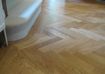 Oak herringbone parquet blocks 350mm long x 70mm wide with an oak border following the curve of the curtail step of the staircase in Nottingham