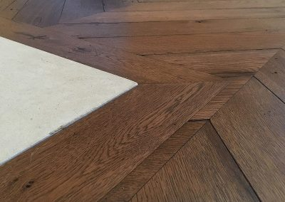 Reclaimed oak chevron floor with border around a stone hearth