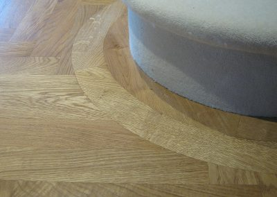 European oak herringbone parquet floor with a curved border around a curtail step of a staircase in Papplewick Nottinghamshire