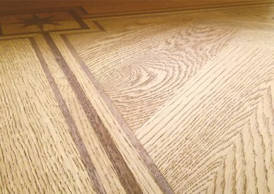 Oak herringbone parquet with a three line black walnut border