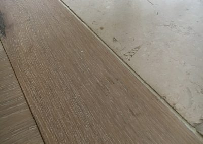 Engineered flooring threshold with a flexible expansion joint meeting a stone floor