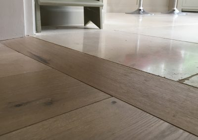 Engineered wooden flooring ramped threshold meeting a stone floor